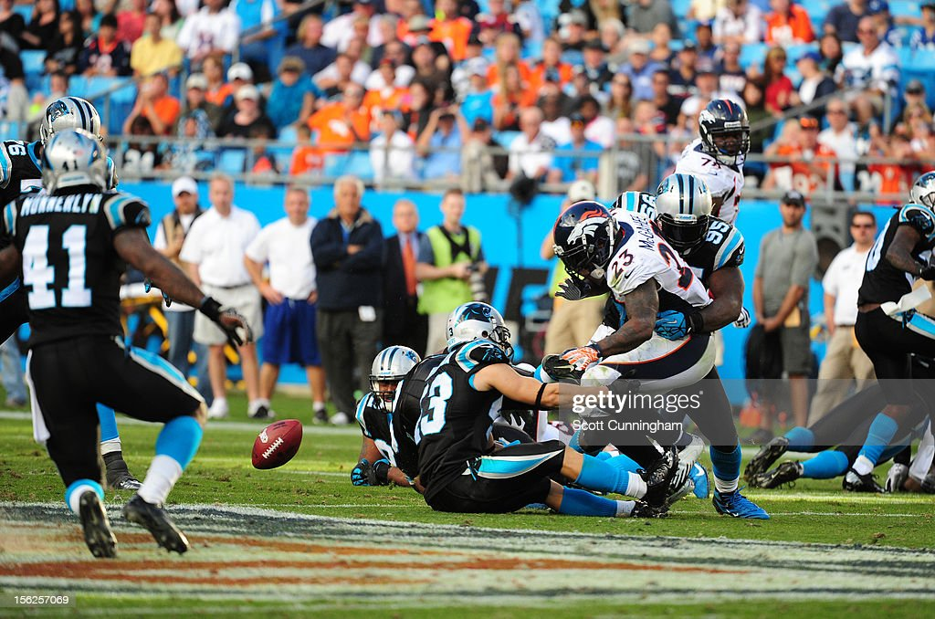 Willis McGahee #23 of the Denver Broncos fumbles after being hit by Charles Johnson #95 of the Carolina Panthers at Bank of America Stadium on November 11, 2012 in Charlotte, North Carolina.