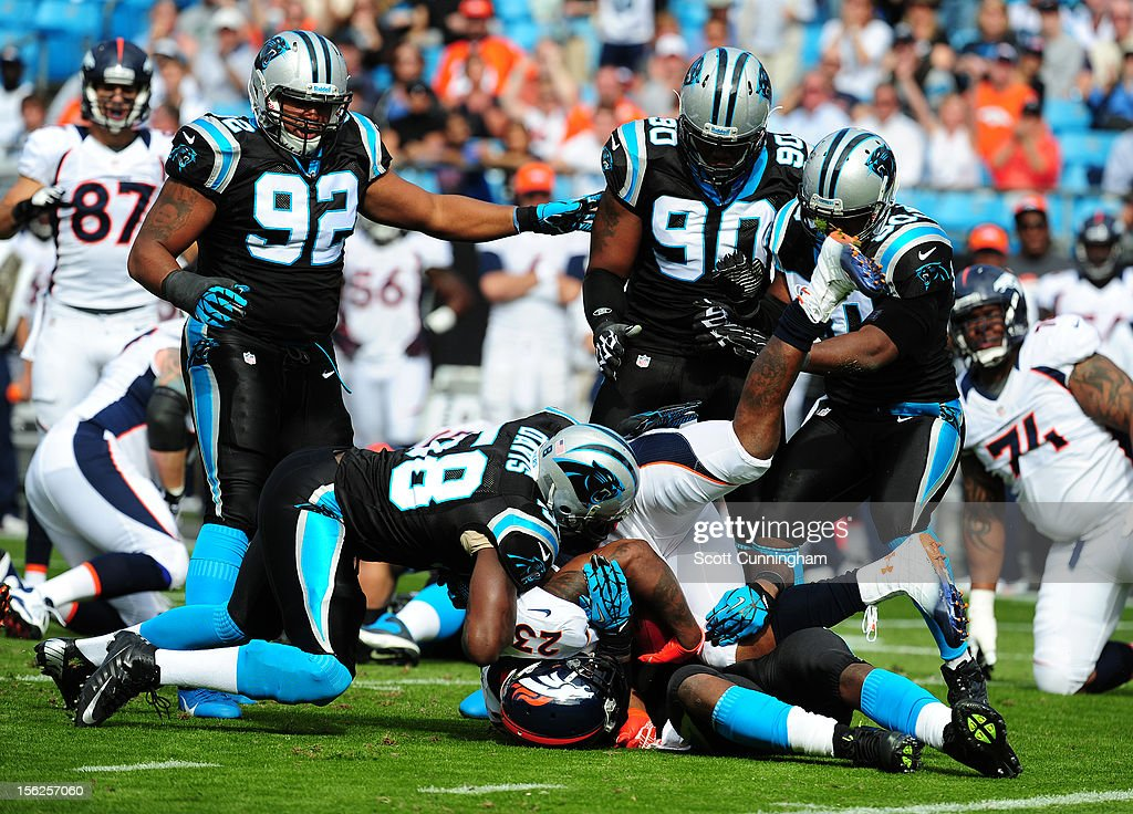 Willis McGahee #23 of the Denver Broncos is tackled by Thomas Davis #58 and Charles Johnson #95 of the Carolina Panthers at Bank of America Stadium on November 11, 2012 in Charlotte, North Carolina.