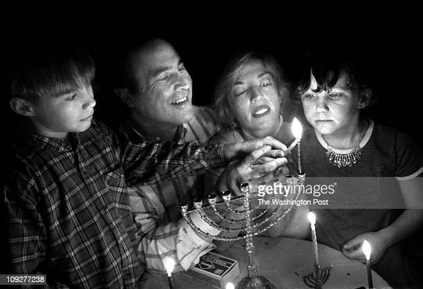 Willow Ave Takoma Park Md Hanukah celebration Group effort for lighting the family Menorah are Larry Asbell and wife Chris Intagliata and their kids...