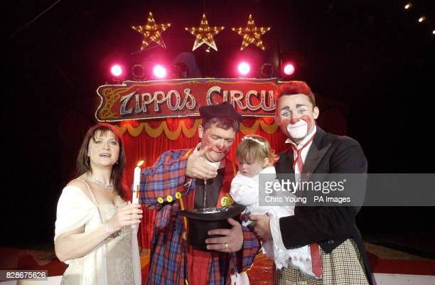 Willow the eighteen month old daughter of Zippo Circus clown Tweedy and his wife Sharon inspect the font fashioned out of a top hat held by Rev Roly...