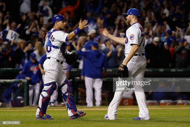 Willson Contreras and Wade Davis of the Chicago Cubs celebrate after beating the Los Angeles Dodgers 32 in game four of the National League...