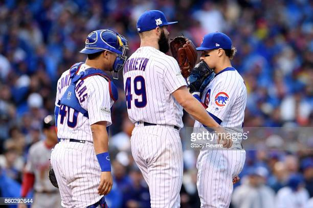 Willson Contreras Jake Arrieta and Javier Baez of the Chicago Cubs meet in the third inning during game four of the National League Division Series...