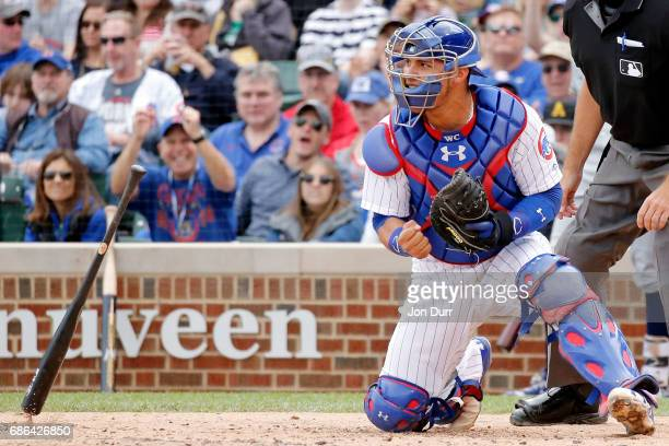 Willson Contreras of the Chicago Cubs celebrates as the bat of Travis Shaw of the Milwaukee Brewers falls to the ground after striking out swinging...