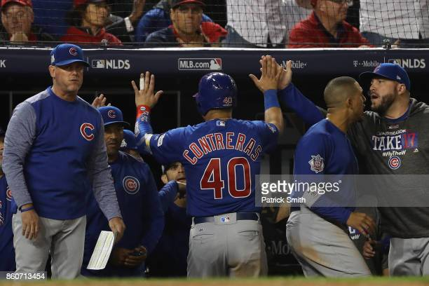 Willson Contreras of the Chicago Cubs celebrates with teammates after scoring on a wild pitch against the Washington Nationals during the third...