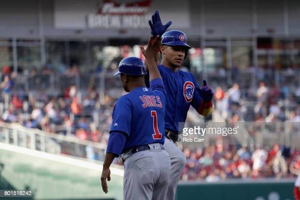 Willson Contreras of the Chicago Cubs celebrates with thrid base coach Gary Jones after hitting a solo home run against the Washington Nationals in...