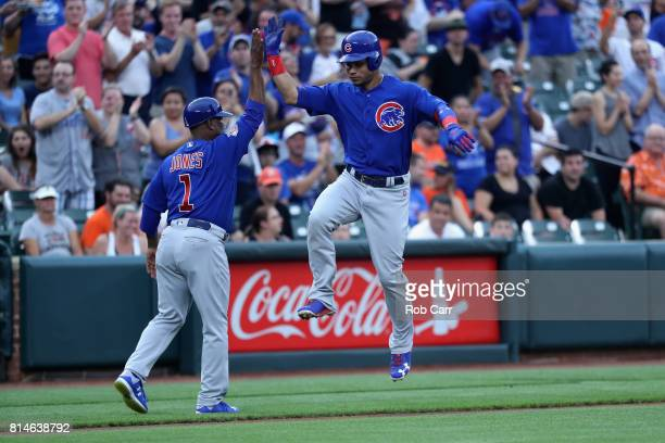 Willson Contreras of the Chicago Cubs celebrates with third base coach Gary Jones after hitting a three run home run against the Baltimore Orioles in...