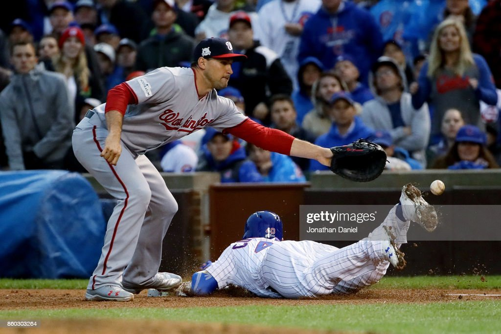 Willson Contreras #40 of the Chicago Cubs dives into first base for a single past Ryan Zimmerman #11 of the Washington Nationals in the fourth inning during game four of the National League Division Series at Wrigley Field on October 11, 2017 in Chicago, Illinois.