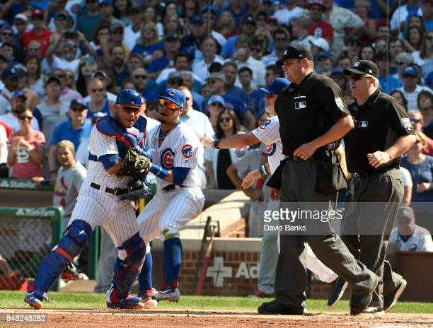 Willson Contreras of the Chicago Cubs is restrained by Javier Baez of the Chicago Cubs as he was thrown out of the game umpire Jordan Baker on...