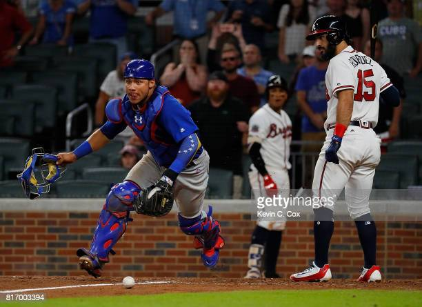 Willson Contreras of the Chicago Cubs runs out around Sean Rodriguez of the Atlanta Braves to field a wild pitch by Wade Davis in the ninth inning at...