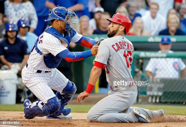 Willson Contreras of the Chicago Cubs tags out Matt Carpenter of the St Louis Cardinals at home for the final out of the first inning at Wrigley...