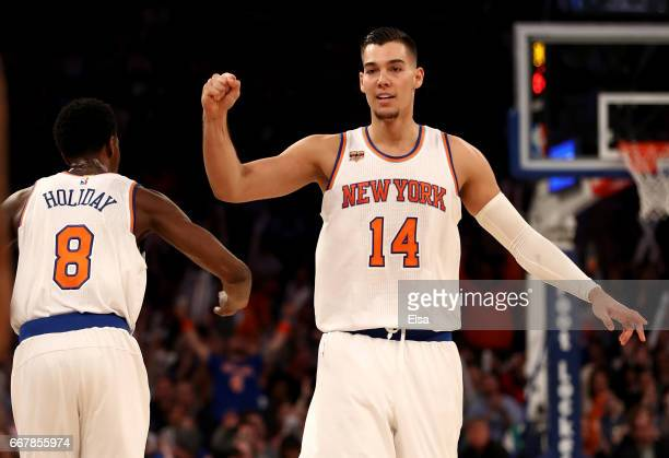 Willy Hernangomez of the New York Knicks celebrate with teammate Justin Holiday in the second half against the Philadelphia 76ers at Madison Square...