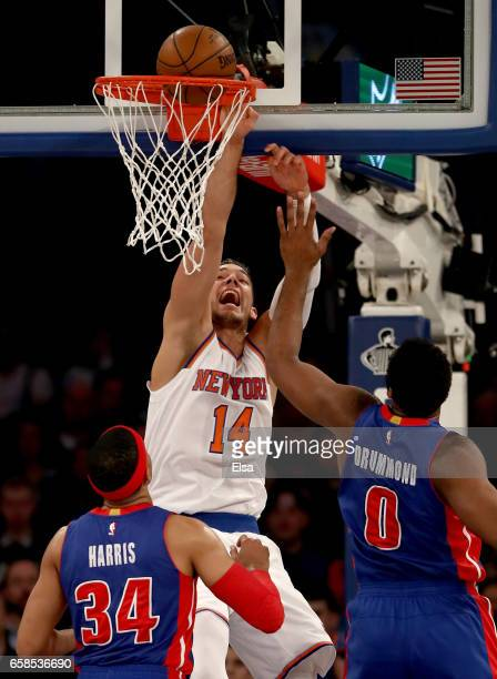 Willy Hernangomez of the New York Knicks makes the shot and draws the foul as Tobias Harris and Andre Drummond of the Detroit Pistons defend at...