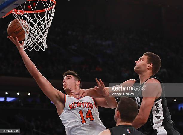 Willy Hernangomez of the New York Knicks puts up a layup against Brook Lopez of the Brooklyn Nets during the second half at Madison Square Garden on...