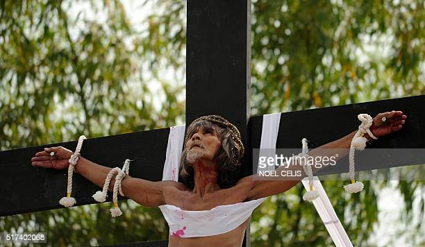 Willy Salvador hangs from a cross as part of his penitence during a reenactment of the crucifixion of Jesus Christ for Good Friday celebrations ahead...