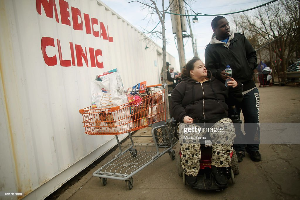 Wilma Marrero and her son Joseph Kendall (R) leave with their goods after waiting in line about five hours to obtain food and other items from a distribution point in the Coney Island neighborhood on November 20, 2012 in the Brooklyn borough of New York City. The Coney Island area was hard hit by Superstorm Sandy.