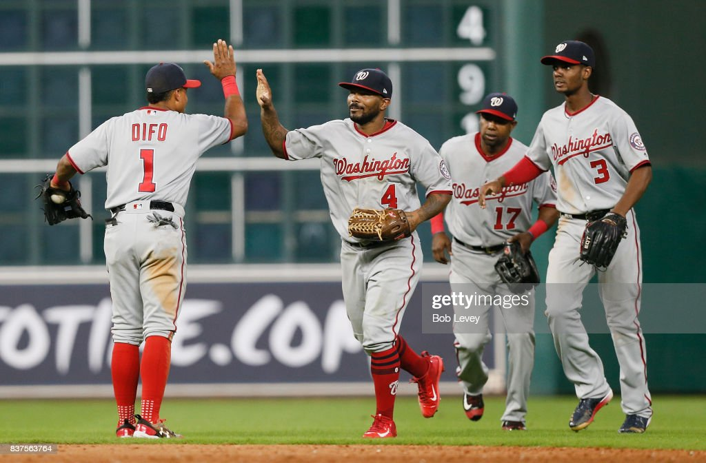 Wilmer Difo #1 of the Washington Nationals high fives Howie Kendrick #4 along with Alejandro De Aza #17 and Michael Taylor #3 to end the game against the Houston Astros at Minute Maid Park on August 22, 2017 in Houston, Texas.