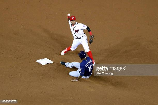 Wilmer Difo of the Washington Nationals throws to first base as Domingo Santana of the Milwaukee Brewers slides into second during the game at...