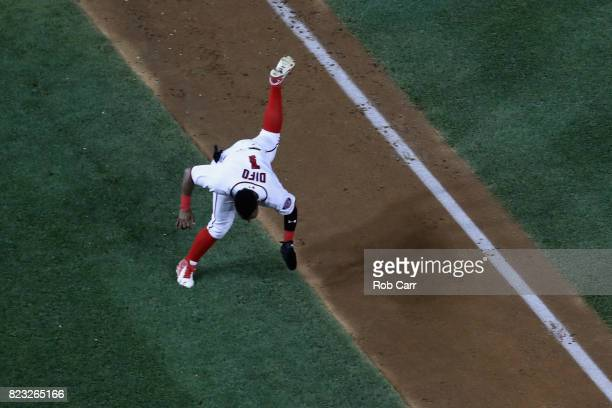 Wilmer Difo of the Washington Nationals trips on the base path while coming into score a run in the eighth inning against the Milwaukee Brewers at...