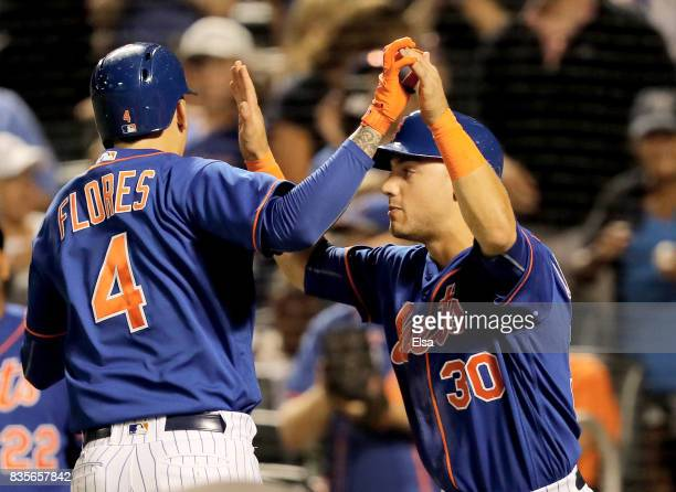 Wilmer Flores and Michael Conforto of the New York Mets celebrate after they both scored on a home run from Flores in the sixth inning against the...