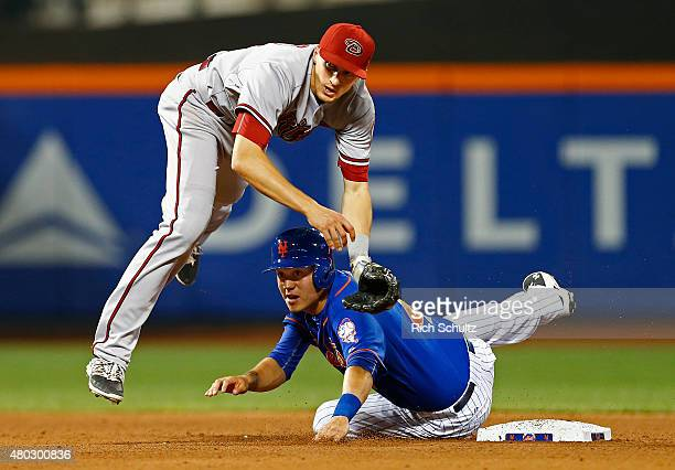 Wilmer Flores of the New York Mets slides into shortstop Nick Ahmed of the Arizona Diamondbacks who throws to first base to get Lucas Duda for a...