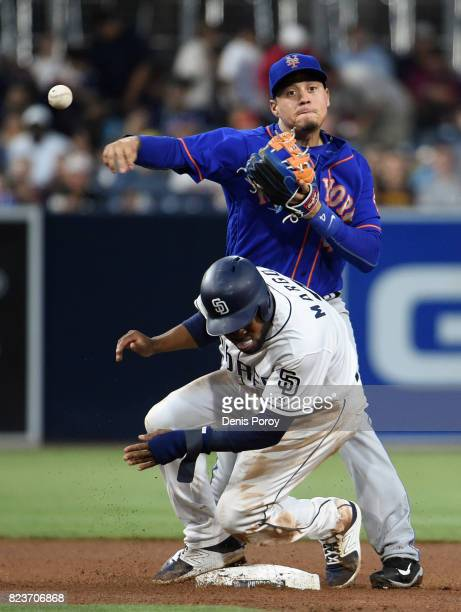 Wilmer Flores of the New York Mets throws over Manuel Margot of the San Diego Padres as he turns a double play during the fourth inning of a baseball...