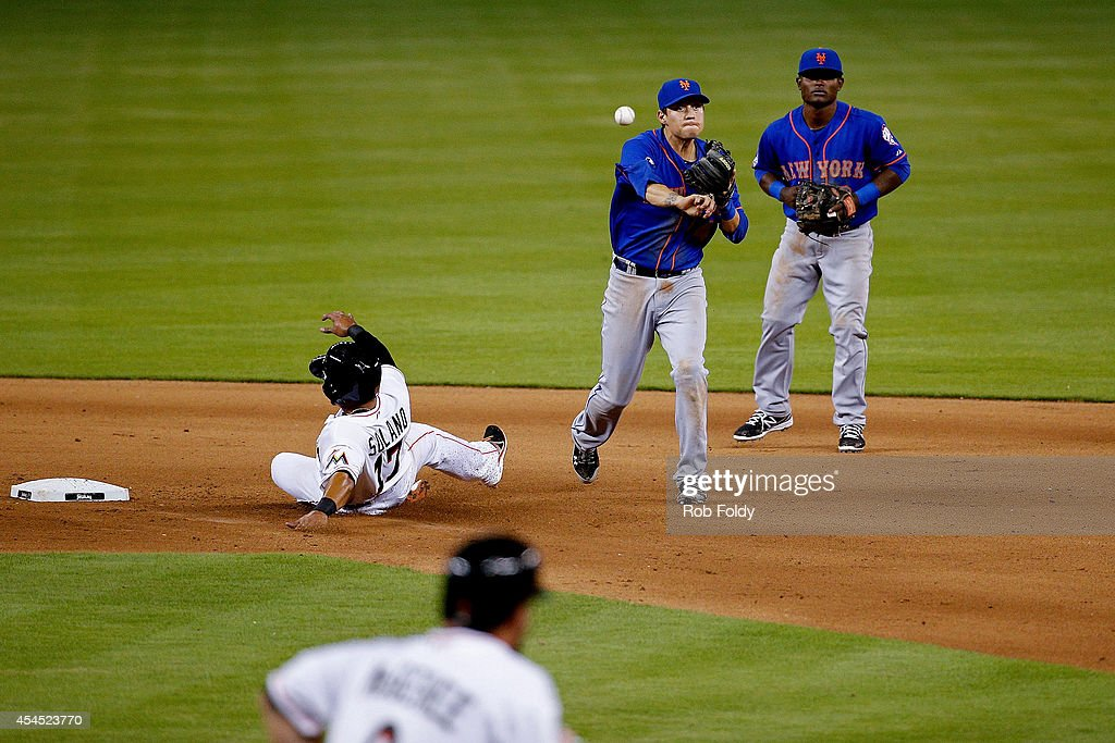 <a gi-track='captionPersonalityLinkClicked' href=/galleries/search?phrase=Wilmer+Flores&family=editorial&specificpeople=5970686 ng-click='$event.stopPropagation()'>Wilmer Flores</a> #4 of the New York Mets turns a double play over Donovan Solano #17 of the Miami Marlins during the eighth inning of the game at Marlins Park on September 2, 2014 in Miami, Florida.