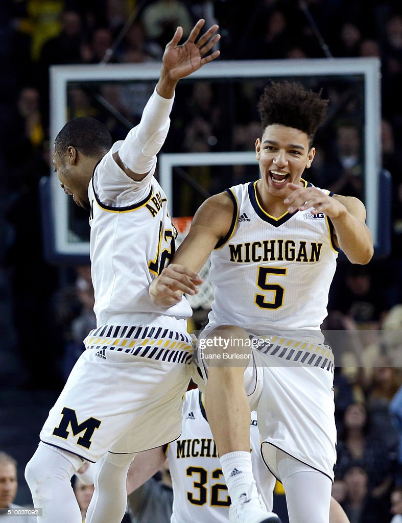 D.J. Wilson #5 and Muhammad-Ali Abdur-Rahkman #12 of the Michigan Wolverines celebrate after defeating Purdue 61-56 at Crisler Arena on February 13, 2016 in Ann Arbor, Michigan.