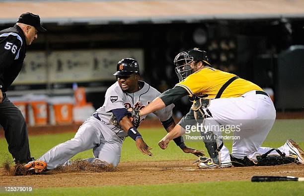 Wilson Betemit of the Detroit Tigers is tagged out at home plate by Landon Powell of the Oakland Athletics in the six inning during an MLB baseball...