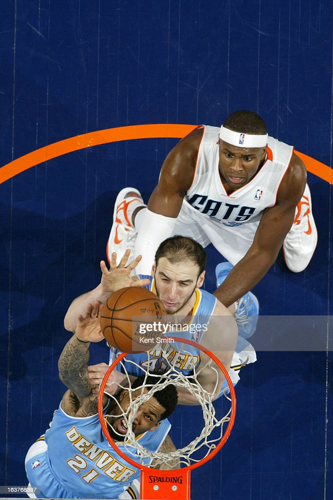 Wilson Chandler #21 and Kosta Koufos #41 of the Denver Nuggets go up for a rebound against Brendan Haywood #33 of the Charlotte Bobcats at the Time Warner Cable Arena on February 23, 2013 in Charlotte, North Carolina.