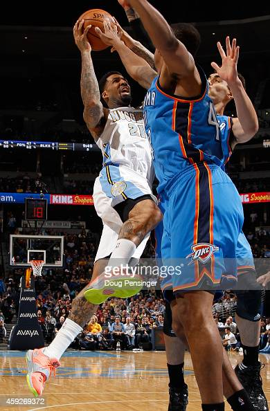 Wilson Chandler of the Denver Nuggets gets off a shot against Lance Thomas and Steven Adams of the Oklahoma City Thunder at Pepsi Center on November...
