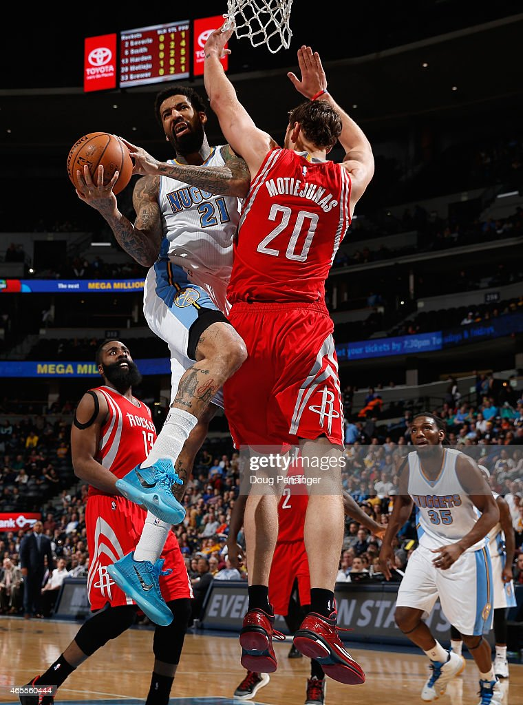 Wilson Chandler of the Denver Nuggets goes up for a shot against Donatas Motiejunas of the Houston Rockets at Pepsi Center on March 7 2015 in Denver...