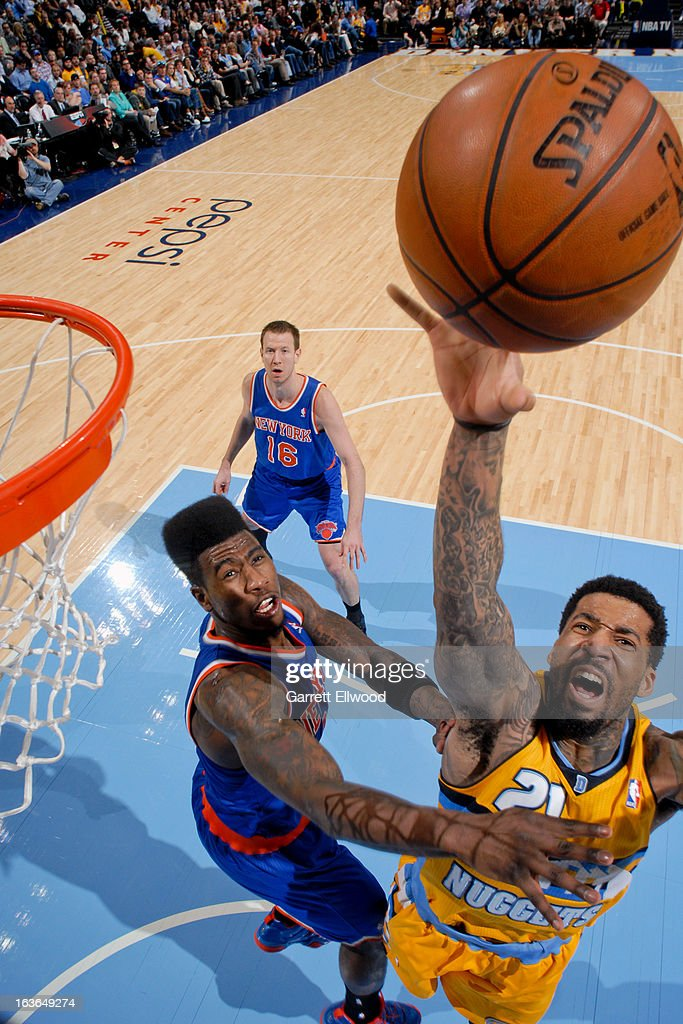 Wilson Chandler #21 of the Denver Nuggets reaches for a rebound against Iman Shumpert #21 of the New York Knicks on March 13, 2013 at the Pepsi Center in Denver, Colorado.
