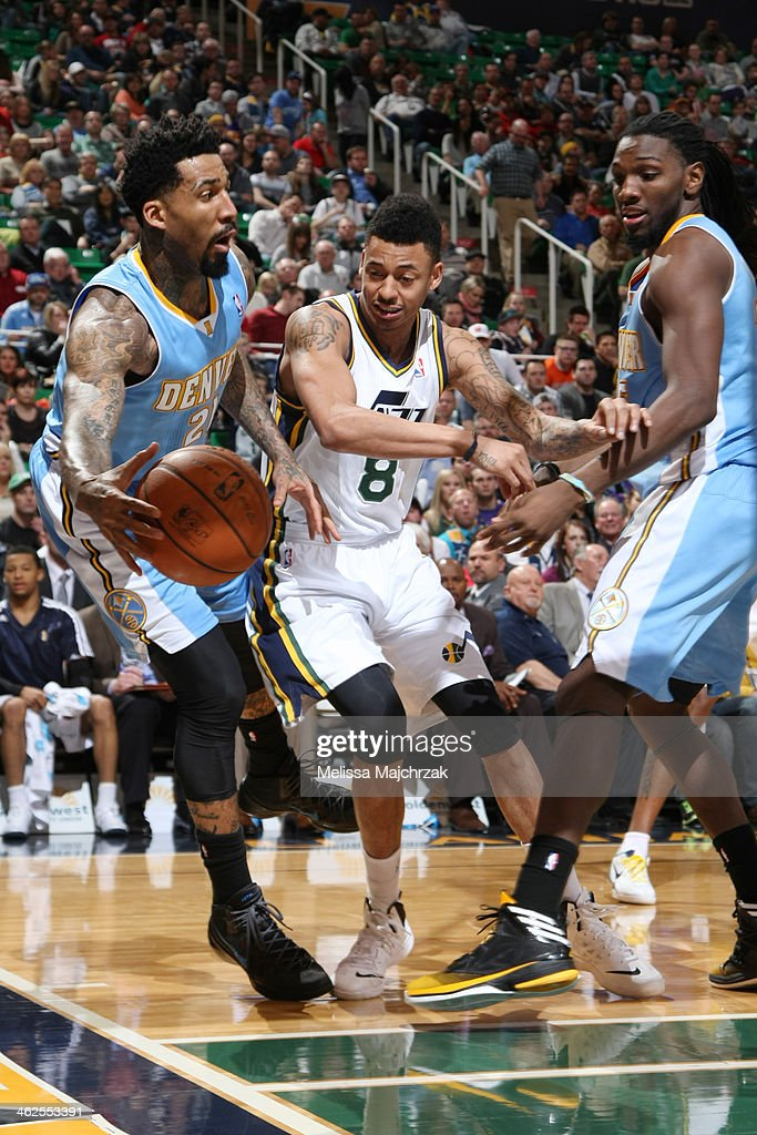 Wilson Chandler #21 of the Denver Nuggets saves the ball from going out of bounds against Diante Garrett #8 of the Utah Jazz at EnergySolutions Arena on January 13, 2014 in Salt Lake City, Utah.