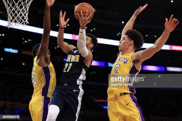 Wilson Chandler of the Denver Nuggets splits the defense of Lonzo Ball and Thomas Bryant of the Los Angeles Lakers during the second half of a...