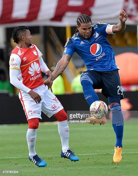 Wilson Morelo of Millonarios struggles for the ball with Roman Torres of Independiente Santa Fe during a match between Independiente Santa Fe and...