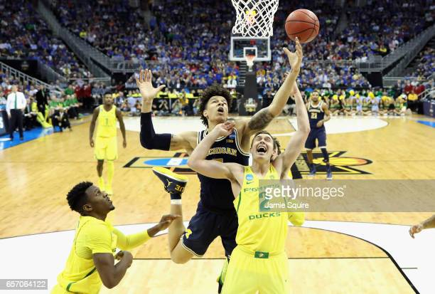 J Wilson of the Michigan Wolverines and Casey Benson of the Oregon Ducks battle for the ball in the second half during the 2017 NCAA Men's Basketball...