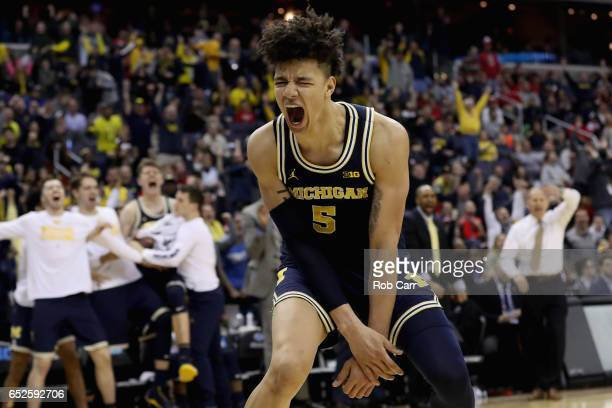 J Wilson of the Michigan Wolverines celebrates after dunking the ball against the Wisconsin Badgers in the second half during the Big Ten Basketball...
