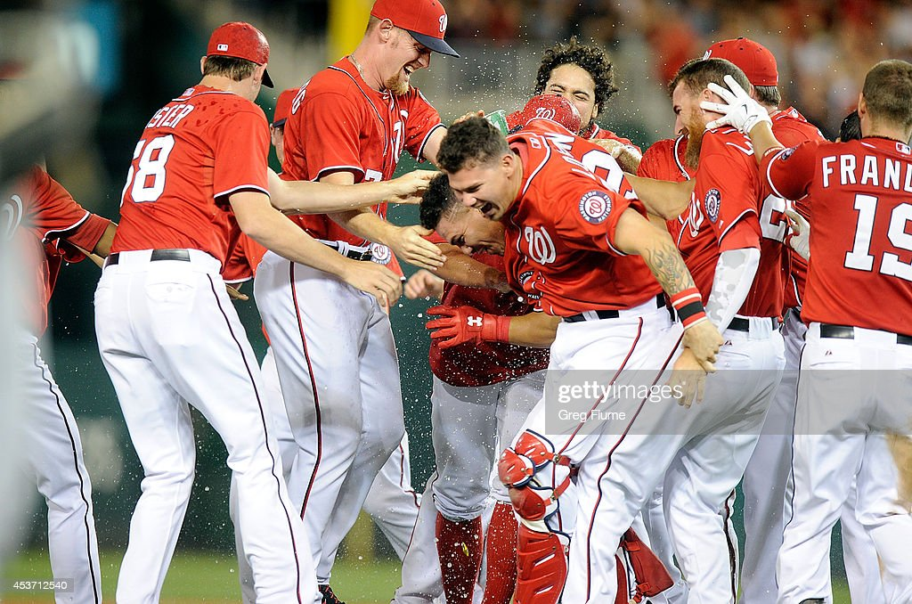 Wilson Ramos #40 of the Washington Nationals is mobbed by teammates after driving in the game winning run in the ninth inning against the Pittsburgh Pirates at Nationals Park on August 16, 2014 in Washington, DC. Washington won the game 4-3.