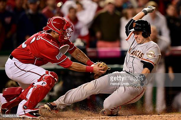 Wilson Ramos of the Washington Nationals tags out Buster Posey of the San Francisco Giants at home plate after Pablo Sandoval of the San Francisco...