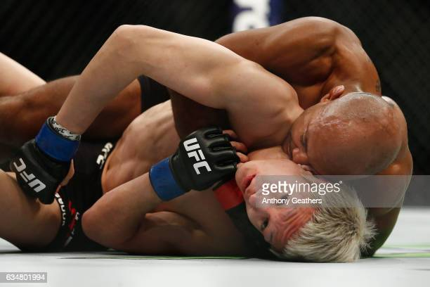 Wilson Reis of Brazil works the choke against Ulka Sasaki of Japan in their flyweight bout during UFC 208 at the Barclays Center on February 11 2017...