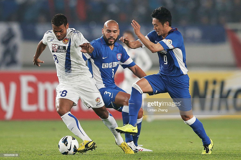 Wilson Rodrigues Fonseca (L) of Vegalta Sendaion challenges Faras Eleilson (C) and Lu Bofei (R) of Jiangsu Sainty during the AFC Champions League match between Jiangsu Sainty and Vegalta Sendai at Nanjing Olympic Sports Center Stadium on March 12, 2013 in Nanjing, China.