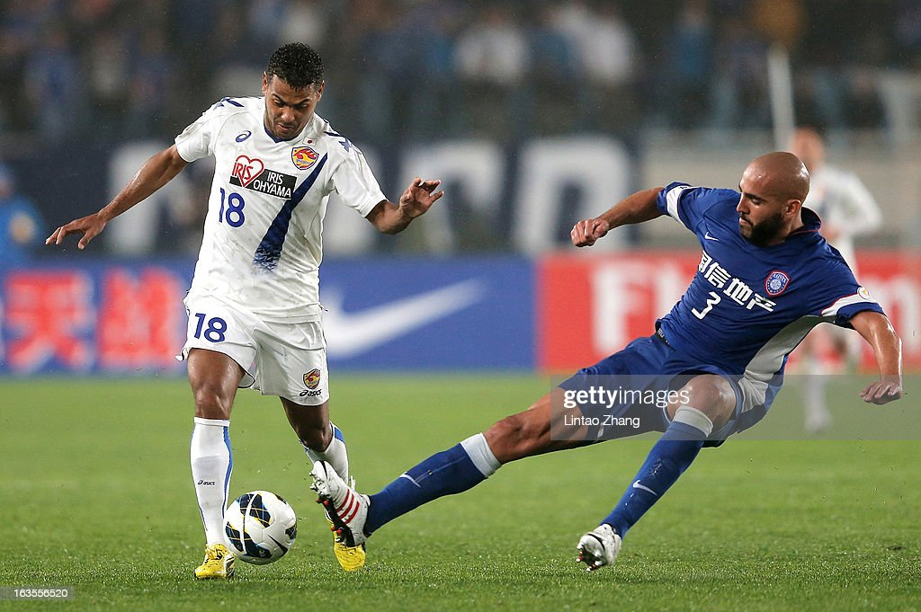 Wilson Rodrigues Fonseca (L) of Vegalta Sendaion challenges Faras Eleilson (R) and of Jiangsu Sainty during the AFC Champions League match between Jiangsu Sainty and Vegalta Sendai at Nanjing Olympic Sports Center Stadium on March 12, 2013 in Nanjing, China.