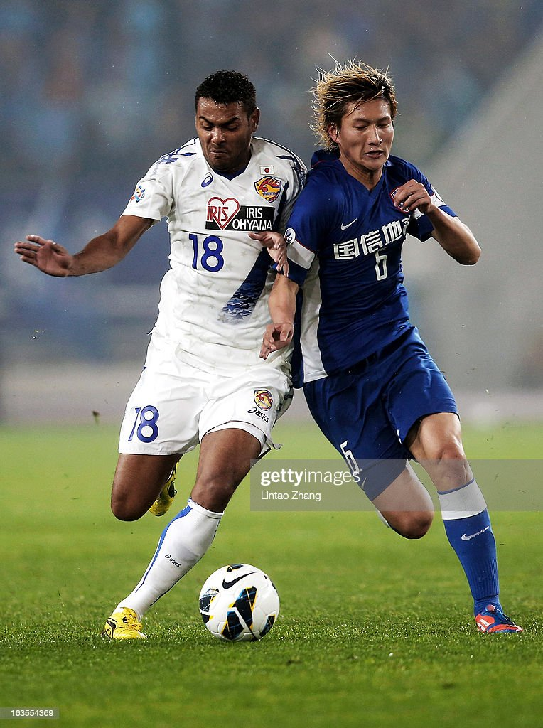 Wilson Rodrigues Fonseca (L) of Vegalta Sendaion challenges Jiang Jiajun of Jiangsu Sainty during the AFC Champions League match between Jiangsu Sainty and Vegalta Sendai at Nanjing Olympic Sports Center Stadium on March 12, 2013 in Nanjing, China.