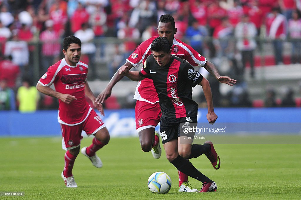 Wilson Tiago (L) of Toluca struggles for the ball with Joe Corona (R) of Tijuana during a match Clausura 2013 Liga MX at Nemesio Diez Stadium on march 30, 2012 in Toluca, Mexico.