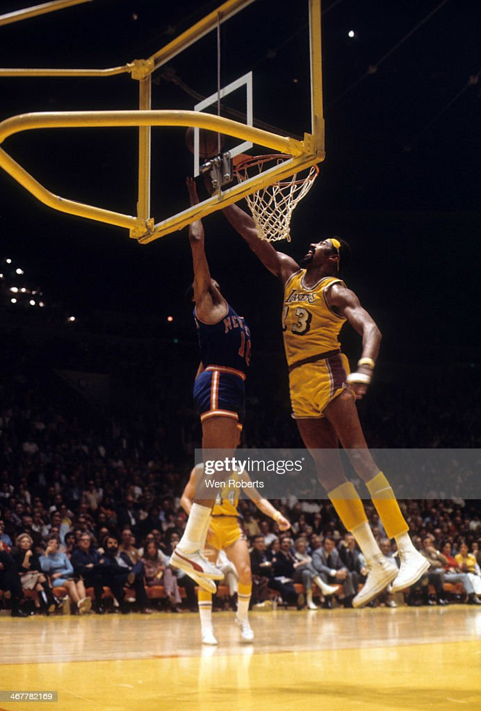 Wilt Chamberlain of the Los Angeles Lakers looks to block the shot attempt of Walt Frazier of the New York Knicks during the 19711972 season at the...