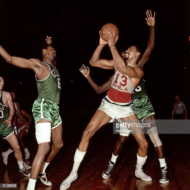 Wilt Chamberlain of the Philadelphia 76ers grabs a rebound against the Boston Celtics during the NBA game circa 1965 in Philadelphia Pennsylvania...