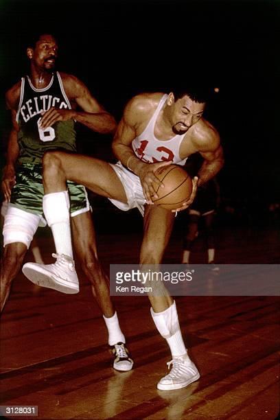 Wilt Chamberlain of the Philadelphia 76ers grabs a rebound against the Boston Celtics during the NBA game circa 1965 in Philadelphia Pennsylvania...
