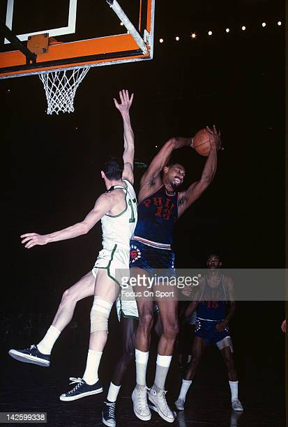 Wilt Chamberlain of the Philadelphia 76ers grabs a rebound away from John Havlicek of the Boston Celtics during an NBA basketball game circa 1965 at...
