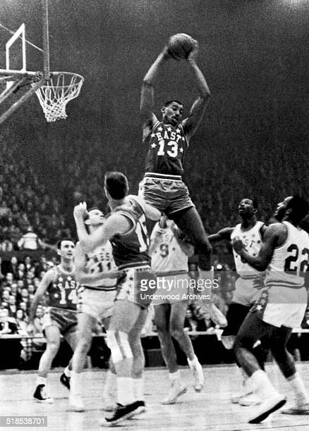 Wilt Chamberlain Philadelphia goes up high to snag a rebound in the NBA AllStar game St Louis Missouri January 16 1962 Below him are Bob Cousey...