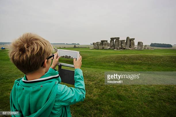 UK, Wiltshire, boy photographing Stonehenge with his digital tablet